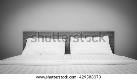 white bedding and pillow in hotel room ,  black and white.