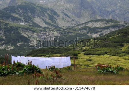 White bedlinen on the line against the background of the Rila mountains in Bulgaria - stock photo