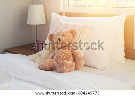 white bedroom decorative with pillows and dolls on bed in the morning