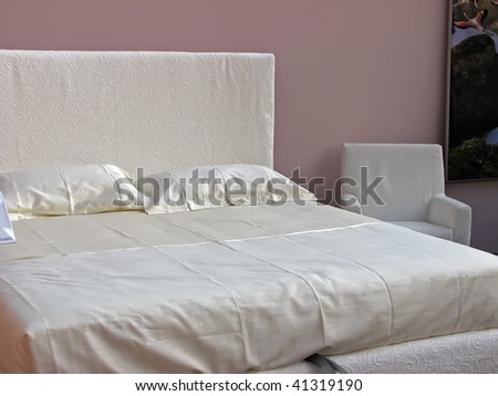 white bedroom. king size bed with white sheets.