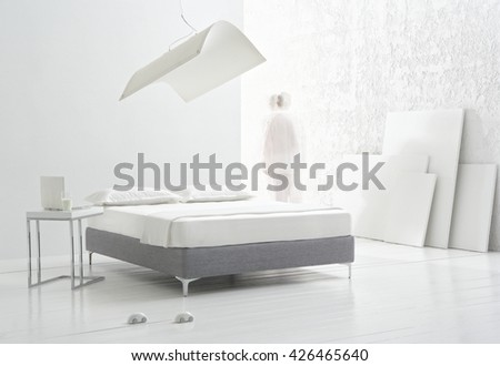 WHITE BEDROOM WITH A MINIMAL DESIGN DOUBLE BED , WHITE SHEET AND PILLOWS , WHITE WOOD FLOOR , ROUGH WHITE WALL WITH WHITE CANVASES AND A BLURRY MAN'S SILHOUETTE  - stock photo