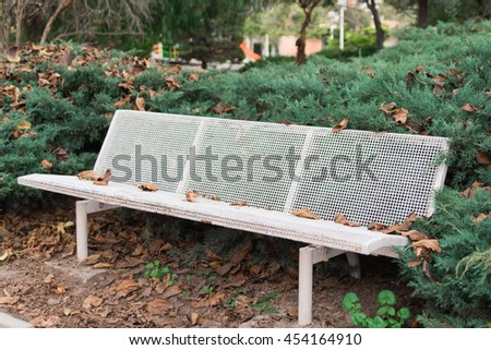 white bench in the garden between green bushes - stock photo