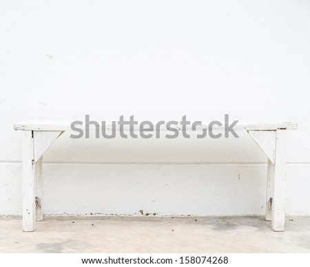 White bench on the white concrete wall - stock photo