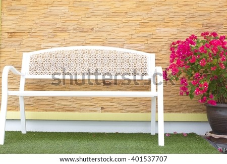 White bench with stone walls and bougainvillea