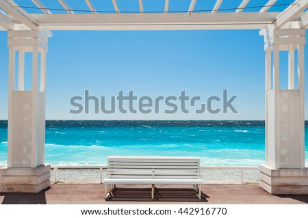 White benches on the Promenade des Anglais in Nice, France. Beautiful turquoise sea and beach - stock photo