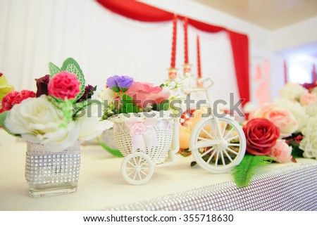 white bicycle basket with flowers on table