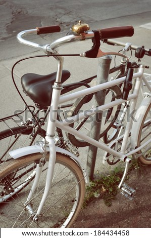 White bicycle parked on the street in Toronto. The saddle is missing - stock photo