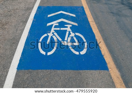 White bicycle sign in painted blue background with white and yellow vertical line for lane separation on asphalt road for bicycle specific safety drive lane