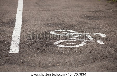 White bicycle symbol drawn on the asphalt separating the cycling lane for bikers in the park.