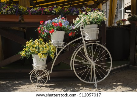 White bicycles with flowers. Close up in a street.