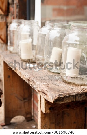 White big candles in glass jars on a retro wooden table outdoors. Simple creative ideas for decorating home and country house. Decorations for windows at Christmas. - stock photo