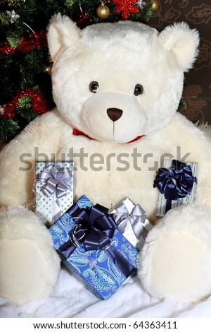 White big teddy bear holding a presents and sitting at the Christmas Tree