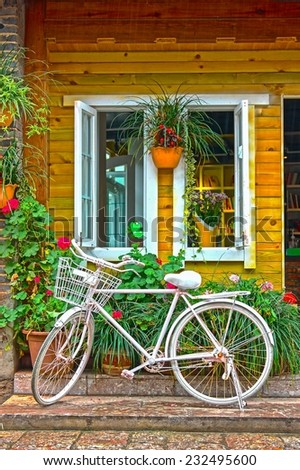 White bike in front of wooden house. - stock photo