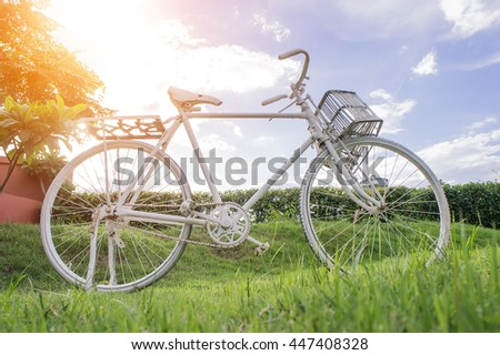 White bike on the lawn background sky and white clouds with light evening.