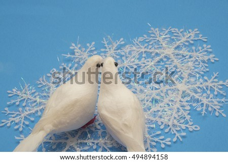 White birds with wintry background for Christmas.Snowflakes and Doves/Christmas decorations on blue background