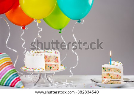 White birthday cake with colorful balloons - stock photo