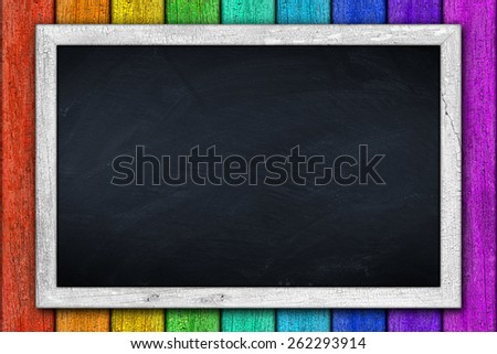 White blackboard on colorful wooden background - stock photo