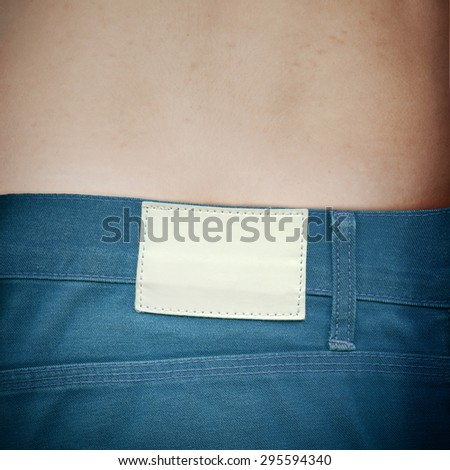 white blank leather label sewed on a blue jeans - stock photo