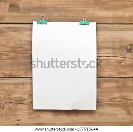 white blank note paper and paper clip on wood background - stock photo