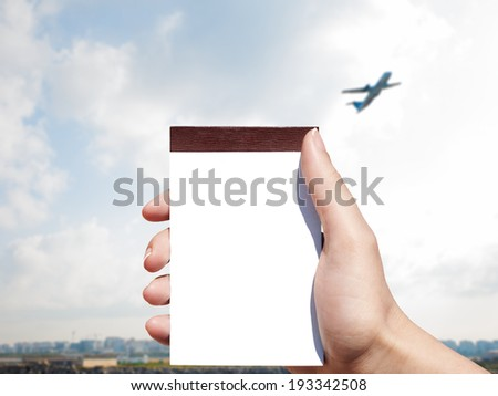 white blank notebook in woman hand and airport background - stock photo