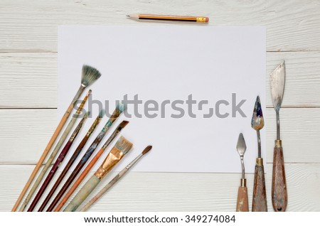 White blank paper sheet with lot of different brushes to paint on a white wooden background, top view - stock photo
