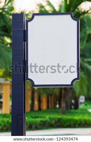 White Blank sign board with blue pole in green park - stock photo