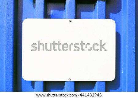 White blank sign mounted on a metal container that is blue.