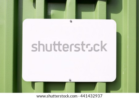 White blank sign mounted on a metal container that is green.