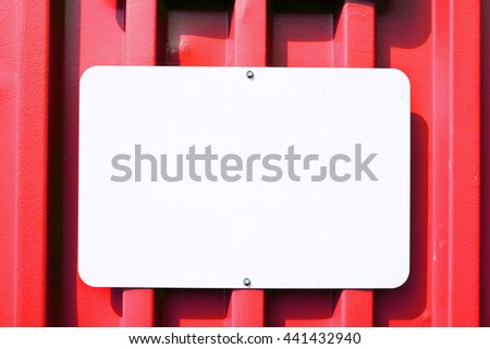 White blank sign mounted on a metal container that is red.