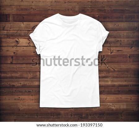 White blank t-shirt on dark wood desk - stock photo