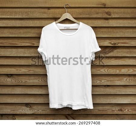 White blank t-shirt on wood wall - stock photo