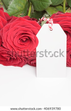 White blank tag with red roses on white background - stock photo