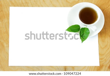White blank with cup of  tea and fresh green leaves on wooden desk - stock photo