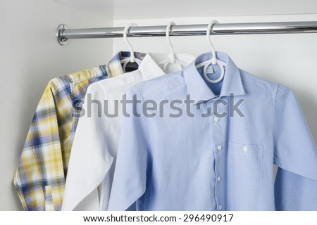 white, blue and checkered clean ironed men's shirts hanging on hangers in the white wardrobe