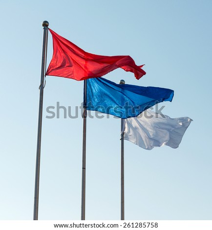 White, blue and red flags against sky. - stock photo