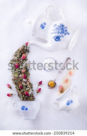 White blue antique sugar bowl with brown sugar and rose petals and magic teapot pouring tea from dry herbs in the cup, Mad Hatter tea party - stock photo