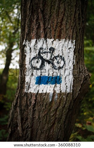 White blue bike sign on tree in forest - stock photo