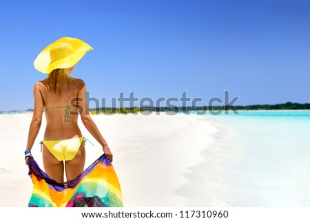 White Blue Yellow. Young girl with colorful sarong walking on white beach. - stock photo