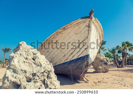 White boat wreck lying on the sand - stock photo