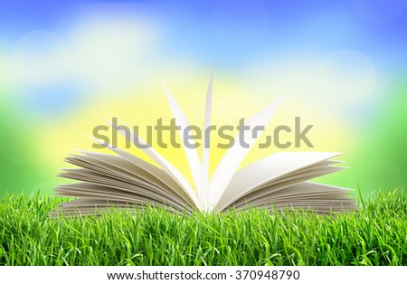 White book in green grass over bright nature background