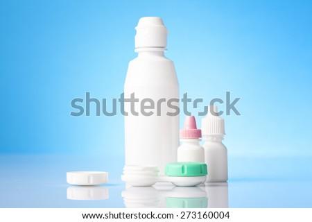 White bottle of eyedrop liquid and dry eyes eye drops on blue background   - stock photo