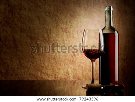 white bottle with red wine and glass and cork with a corkscrew on a old stone
