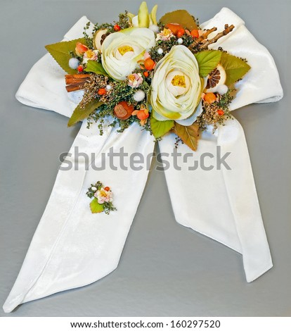 White bow with floral decor at silver gift