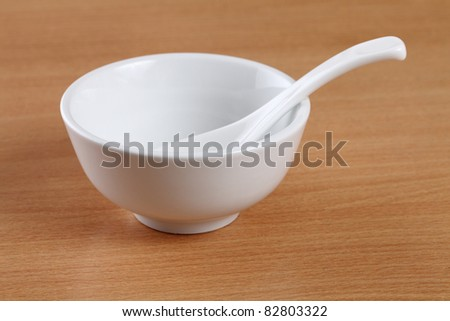 White bowl and spoon on table.