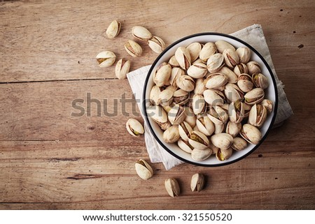 White bowl of pistachios on wooden background - stock photo