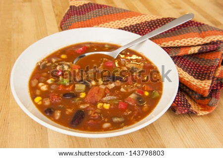White bowl of vegetarian chili on a wood table