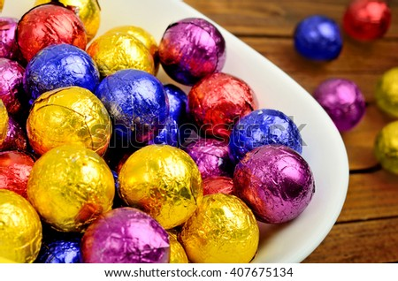 White bowl with colorful chocolate on table - stock photo