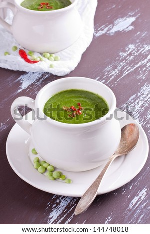 White bowl with cream green pea soup garnished with red chili pepper