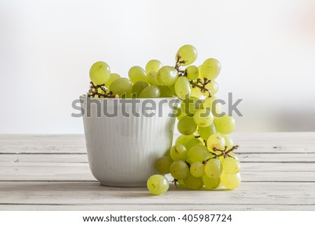 White bowl with green grapes on a wooden table - stock photo