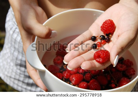 white bowl with red raspberries and currants - stock photo